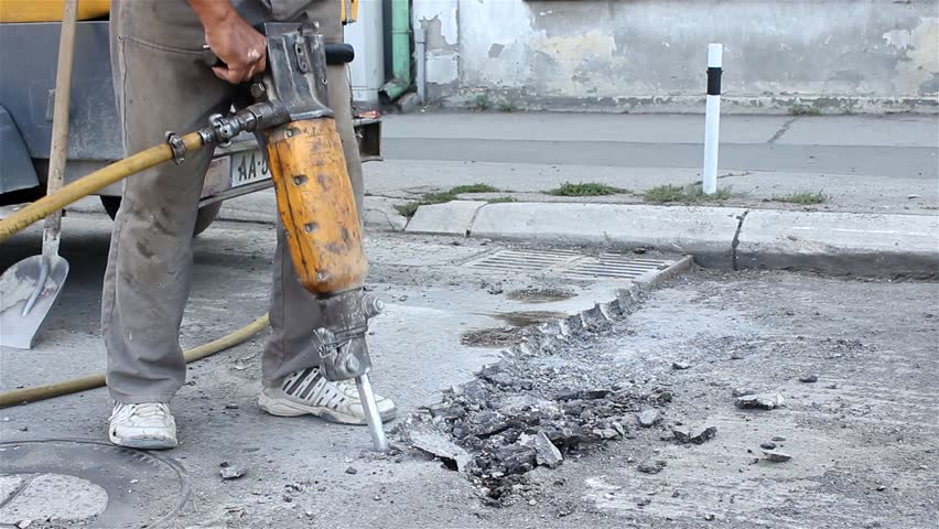 Worker drilling concrete with compressor on the street. Man with the drill breaking up asphalt on the road. Man using a jackhammer. Preparation for paving. Road work. Construction, vibration, close up