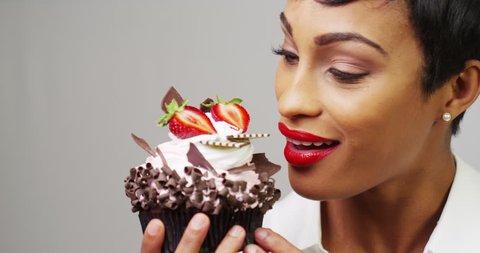 Black woman taking a huge bite out of a fancy dessert