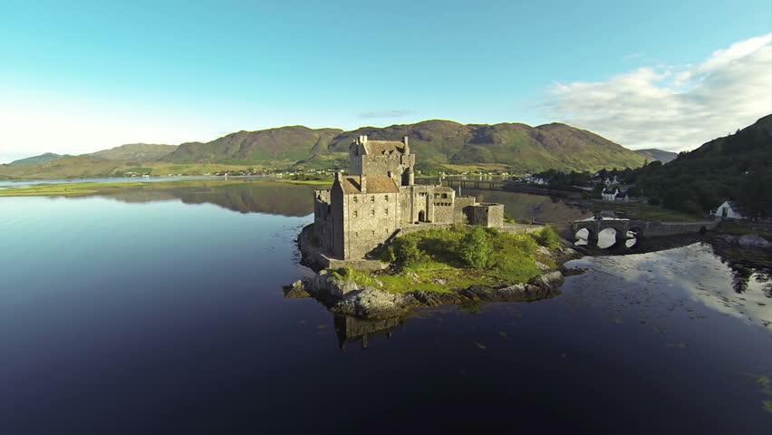 Two scenes of camera flying near serene beautiful EileanDonan Castle near Isle of Skye in Scotland.
