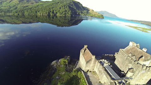Two scenes of camera flying near serene beautiful Eilean Donan Castle near Isle of Skye in Scotland.
