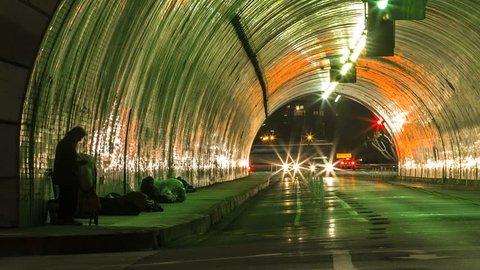 Slow Zoom on Homeless Men Skid Row in City Tunnel Traffic Timelapse