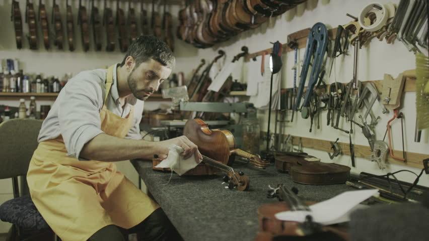 Craftsman in his workshop, making and restoring violins | Shutterstock HD Video #7315597