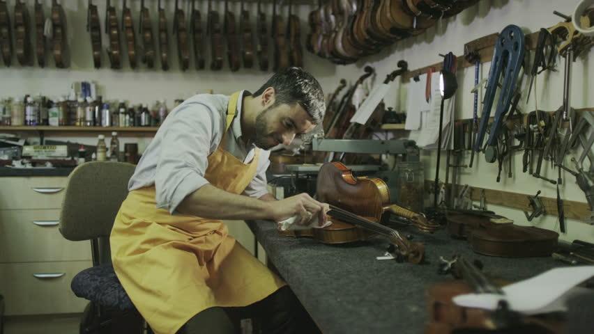 Craftsman in his workshop, making and restoring violins | Shutterstock HD Video #7315663