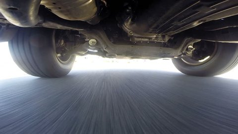 A camera mounted on the underside of a car shows a point of view automobile tires and suspension use while driving.