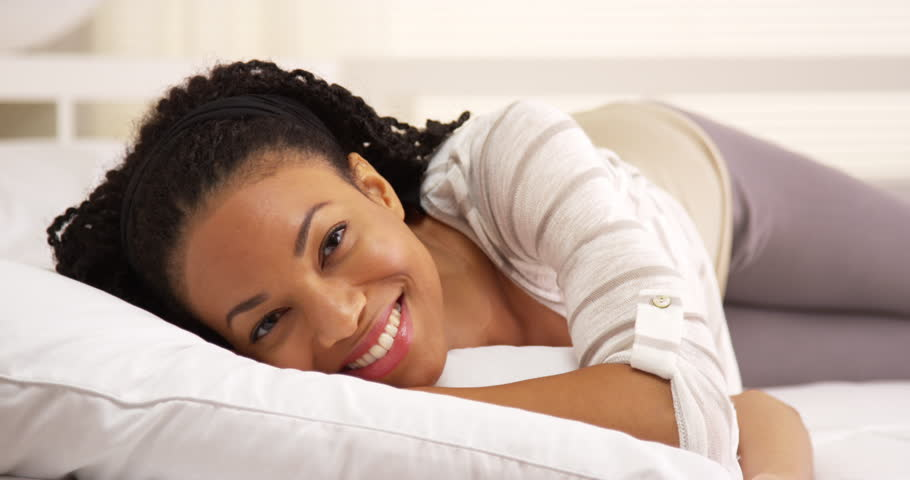 Cute african woman lying on bed looking at camera   Shutterstock HD Video #7320622