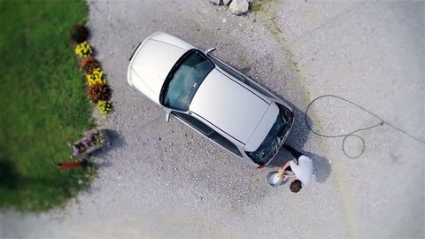 Top air view of car and young man cleaning with sponge.Aerial shot of cleaning car on a sunny day in slow motion putting sponge in to bucket of shampoo water and cleaning back window.