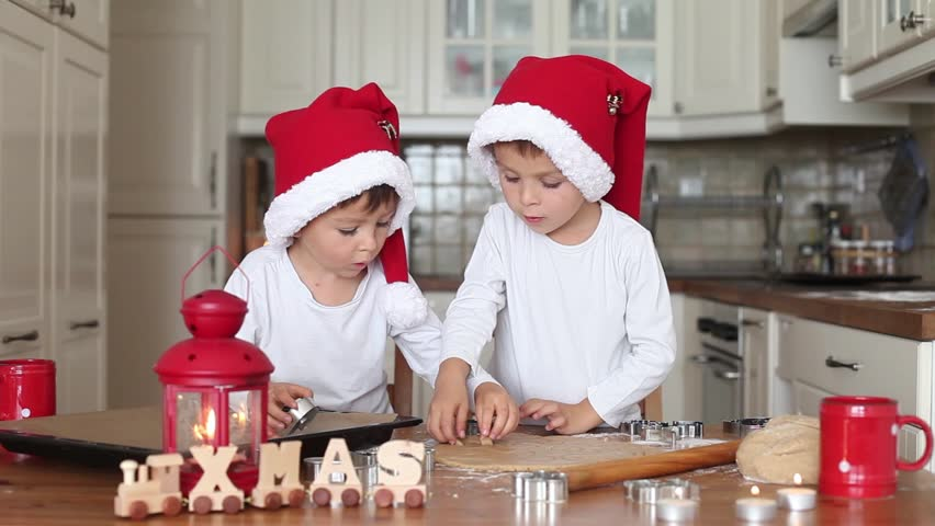 Two kids preparing christmas cookies and put them on baking tray together