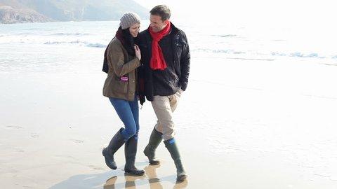 Young Couple Walking Along Winter Beach