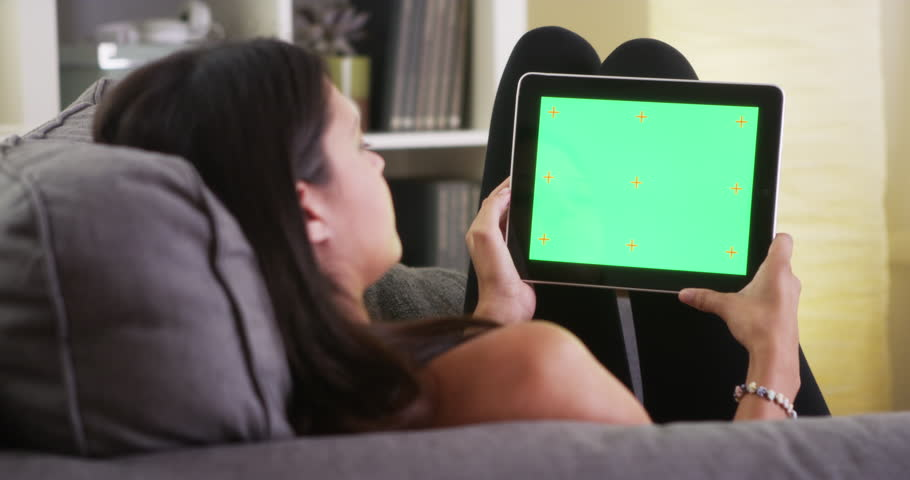 Mixed race girl looking at tablet with green screen