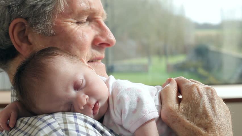 Grandfather Holding Sleeping Newborn Baby Granddaughter