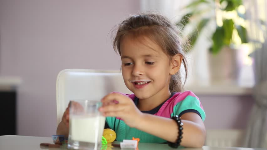 Little Girl is drinking milk from a glass in a modern interior/Girl Is Drinking Milk