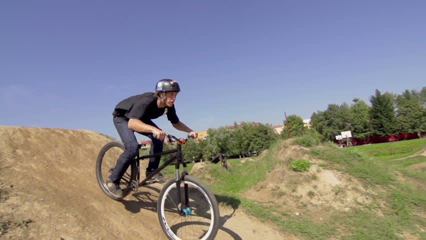 Slow Motion Shot Of A Skilled Bmx Biker Jumping Over The Gap And Spinning Bar
