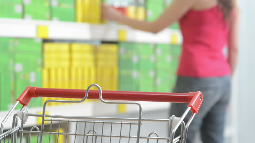 Young woman taking products from store shelves at supermarket with shopping cart on foreground. | Shutterstock HD Video #7435312