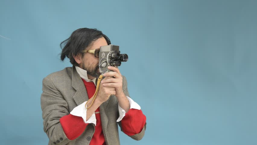 An untidy bizarre man, wearing big glasses, filming a home movie with an antique wind-up super 8 camera, over light blue background