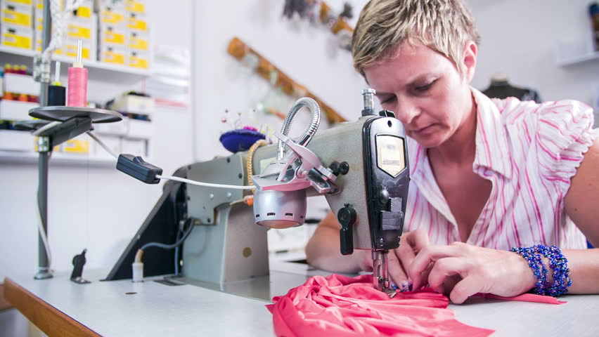 Woman with short hair sewing new dress. Professional tailor in sewing studio making new dress with pink color. Low angle jib shot in slow motion. #7450612