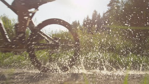 SLOW MOTION: Biker rides through puddle and splashes the camera