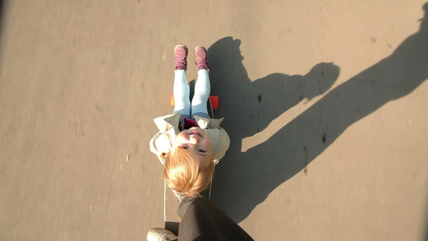 Little girl sits on a longboard, which is run by her dad. View from above. | Shutterstock Video #7465978