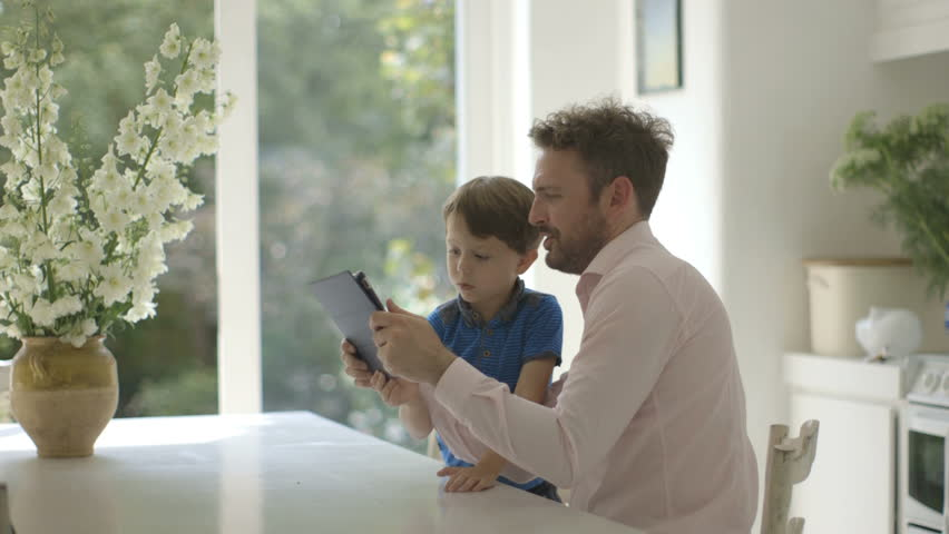 Father and son using digital tablet in domestic room | Shutterstock HD Video #7480642