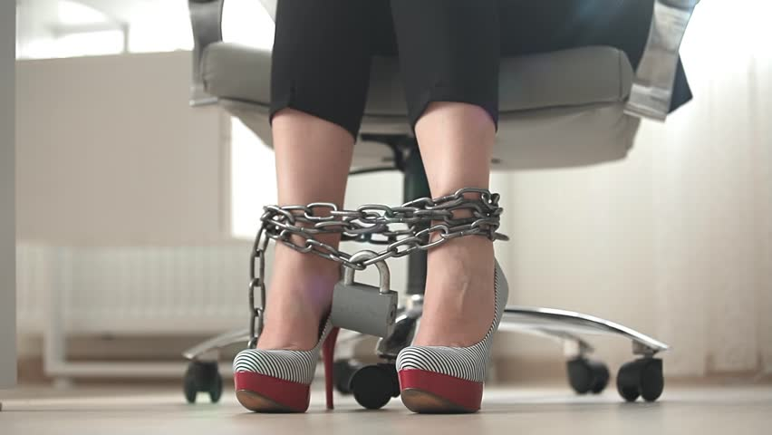 Closeup view of businesswoman tired legs in heels tied by metal chain | Shutterstock HD Video #7481392