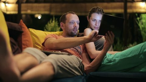 Couple watching something on tablet computer on sofa at home