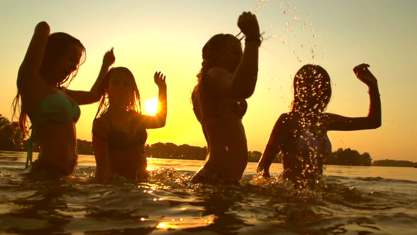 Group of happy girls dancing and playing in water at the beach on sunset. Beauty and joyful teenager friends having fun, spraying over summer sunset. Beach party. Sun flare. Slow motion 1080