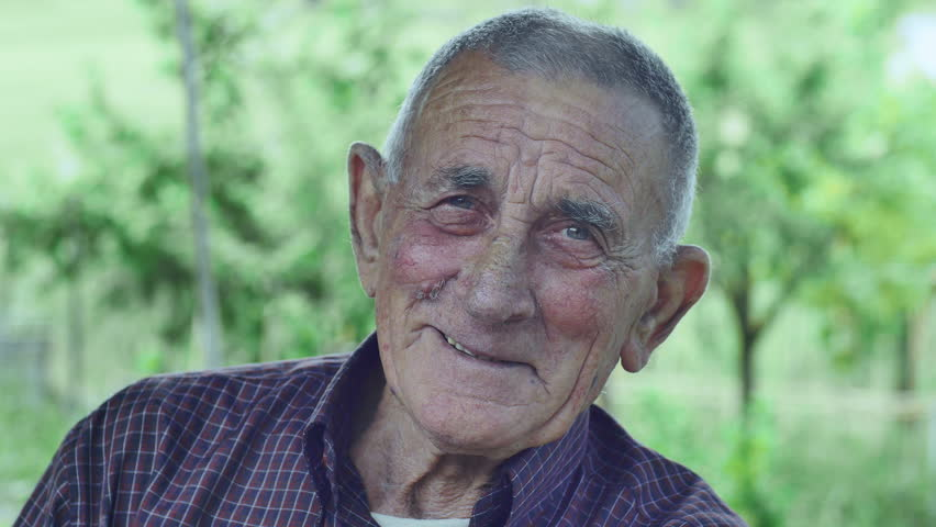 very old person, smiling looks into the camera: green background, countryside
