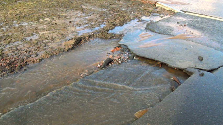 Water flows out from under the asphalt. The accident rupture of the pipeline. | Shutterstock HD Video #7530382