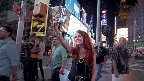 NEW YORK - AUGUST 9, 2014: tourist takes selfie with smartphone in Times Square at night in 4K in New York. Times Square is a major intersection and neighborhood in Manhattan, NYC.