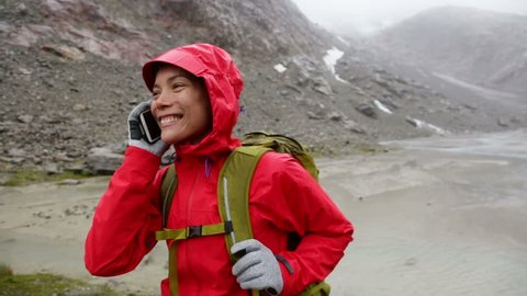 Smart phone woman calling talking on smartphone. Girl on mobile cell phone outside in nature in rain hiking in mountain wearing raincoat. Asian woman smiling laughing in Swiss Alps, Switzerland.