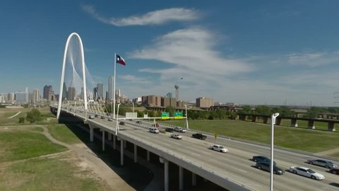 Aerial Dallas Skyline w/Margaret Hunt Hill Bridge on sunny day with a few clouds and Texas Flag flying