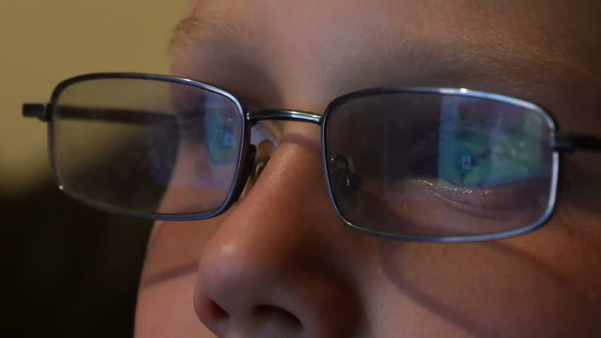 boy in glasses looking at the monitor and the monitor is reflected in the glasses  #7601812