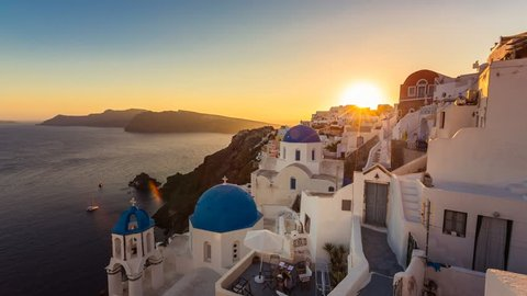 People watching sunset over beautiful town of Oia on the Island of Santorini, Greece