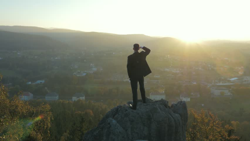 Young businessman on a rock overlooking nature | Shutterstock HD Video #7636732