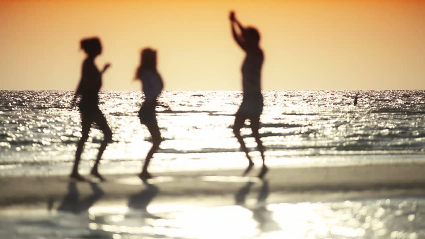 Three carefree girls dancing on the beach at sunset in silhouette