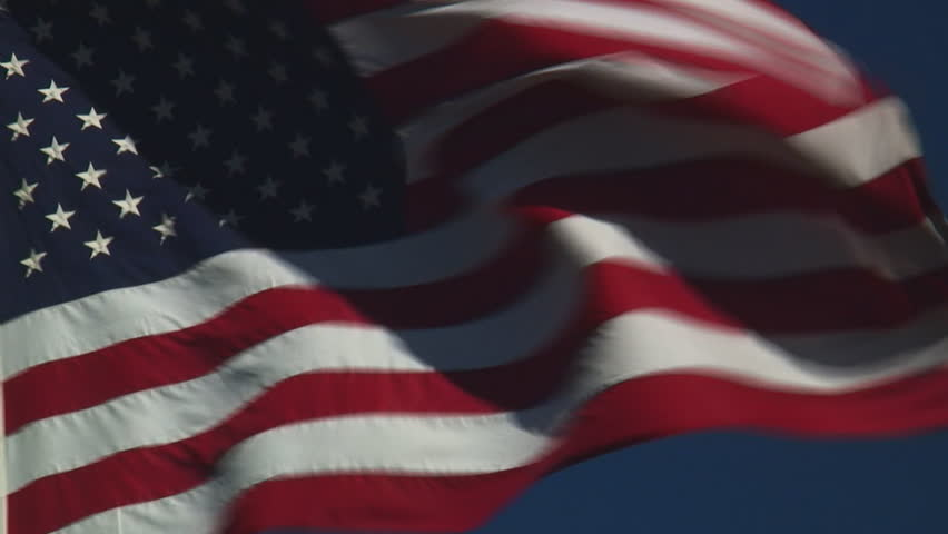real United States of America flag flying flying against clear blue sky - HD, no audio, tight shot