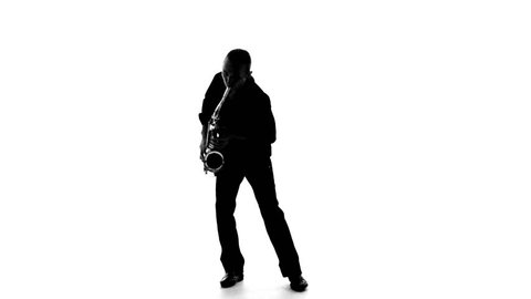 Dark silhouette of a man playing the saxophone on a white background