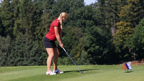 Young female golf player hitting the ball