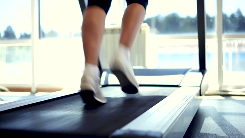 Woman running on a treadmill. Close-up shot/Running on a Treadmill
