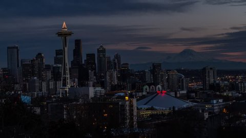A time-lapse sequence of the city of Seattle lighting up at night as the lights of the Space Needle begins to spin. The needle is light up with its Christmas tree lights on top.