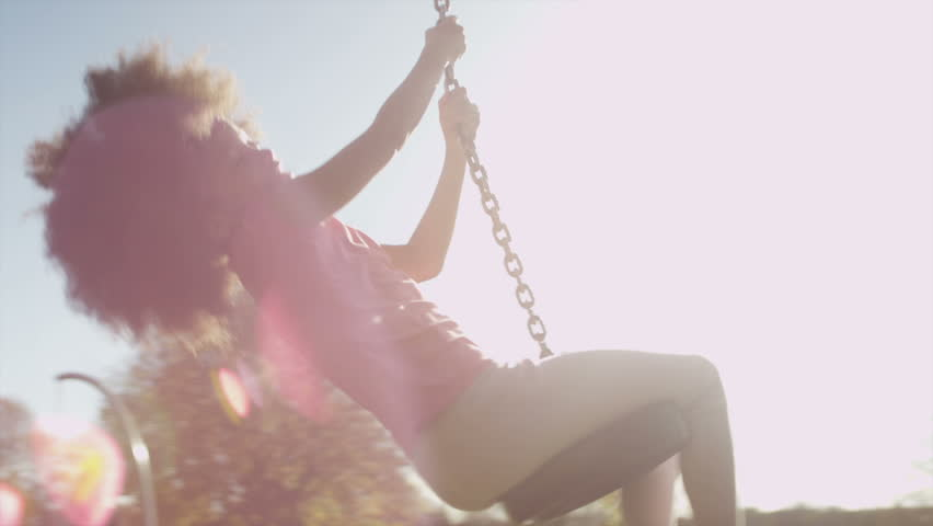 A young girl swinging high on a zip wire ride in a park on a sunny day in slow motion, shot on RED EPIC