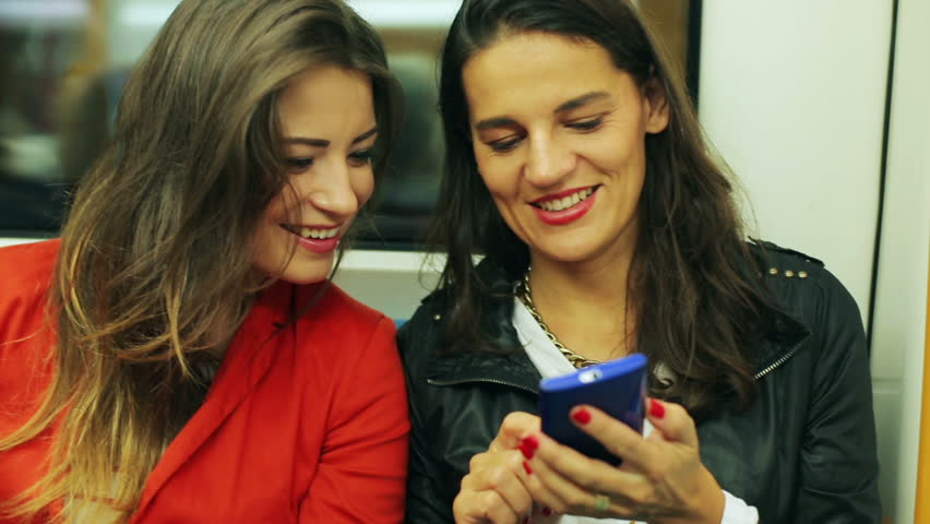 Female friends watching something on smartphone in subway, steadycam shot