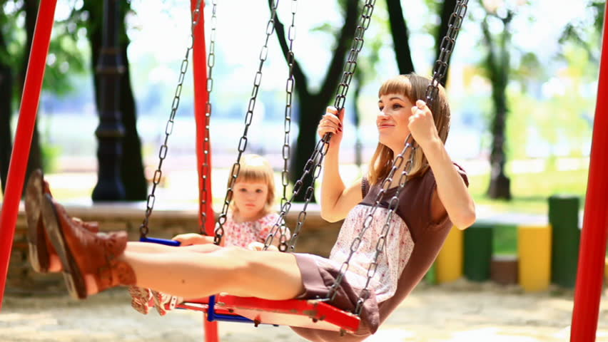 The child and his mother ride on a swing in the park.