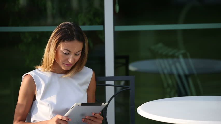 young beautiful business woman sitting at a table with tablet in hands