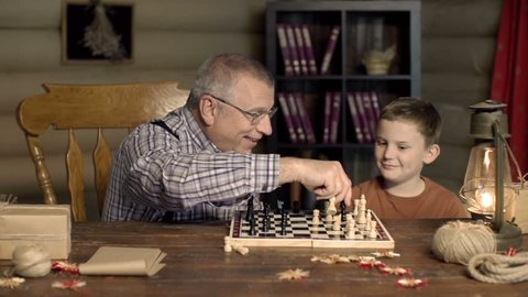 Grandpa happy to capture chess pawn of his grandchild, shocked by his counterstrike