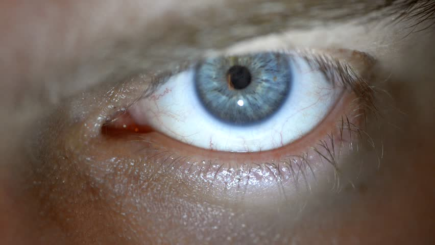 Closeup of blue male eye with contact lens looking at camera. Selective focus. Toned.