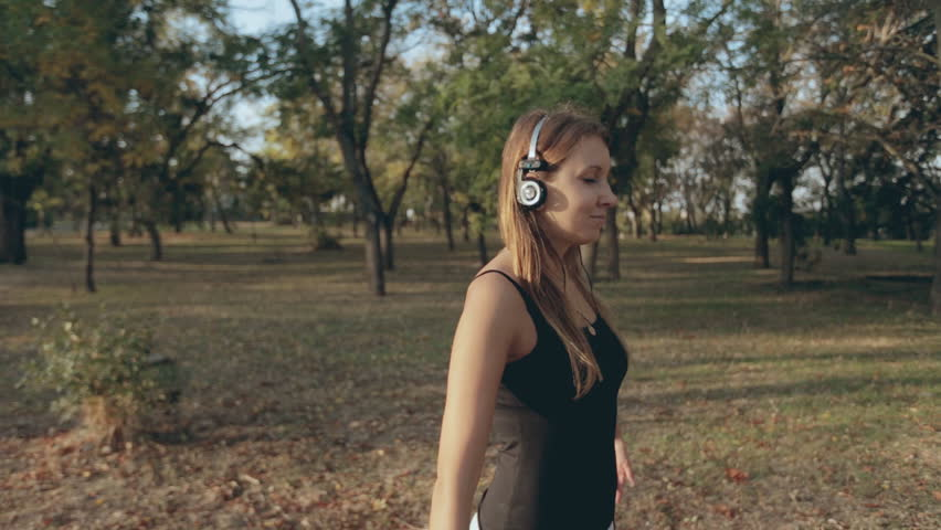 Beautiful young woman doing workout and listening to music on headphones | Shutterstock HD Video #7843960