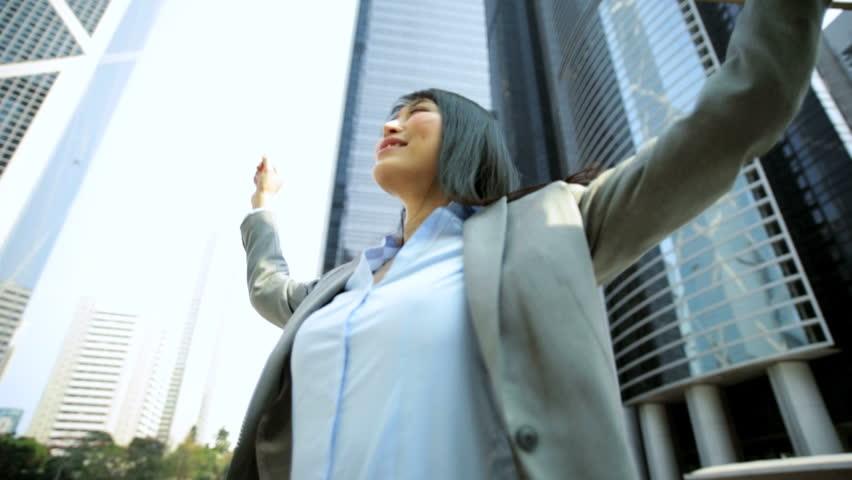 Asian Chinese American businesswoman shares broker outdoors downtown Hong Kong modern city buildings celebrating financial success | Shutterstock HD Video #7851592