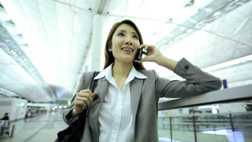 Asian Chinese businesswoman global traveller airport arrival departures hall business smart phone text wireless technology communications   Shutterstock HD Video #7853932