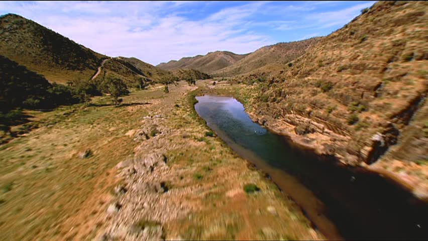 Aerial footage of rugged Australian outback mountain ranges, desert area. Helicopter shots fly through valley. Good shot for 3D terrain tracking VFX. Featuring outback creek. beds, with dirt tracks