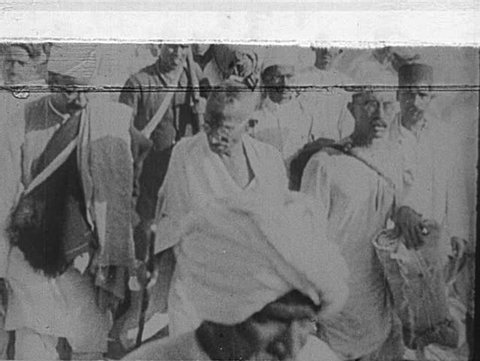 INDIA- CIRCA 1930: Gandhi walks with men dressed in topis and mundus.  Tilt down to massive crowd of men, women, and children in urban street.  Gandhi walks, followed by men, women, and children.